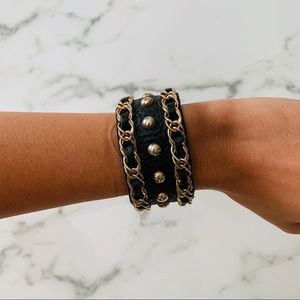 Black leather bracelet with gold detail.